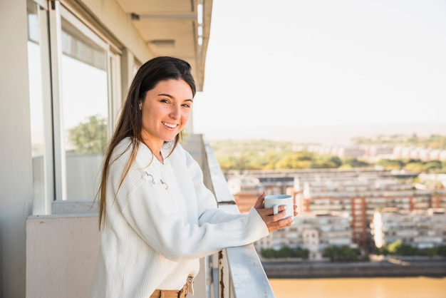 Retrato de una mujer joven sonriente que se coloca en el balcón que sostiene la taza del café con leche