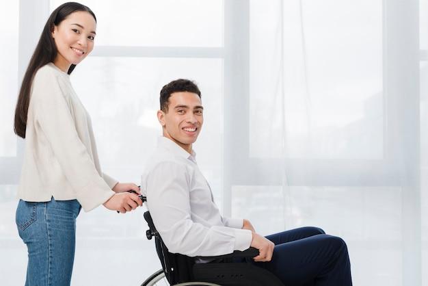 Retrato de una mujer joven sonriente que se coloca detrás del hombre que se sienta en la silla de rueda que mira la cámara