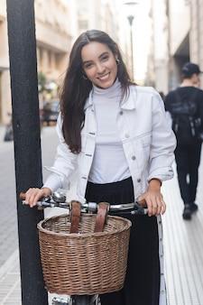 Retrato de la mujer joven sonriente que se coloca con su bicicleta en la calle de la ciudad