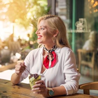 Retrato de una mujer joven sonriente que come muffin de chocolate en el soporte de papel