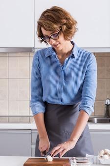 Retrato de una mujer joven sonriente que corta la seta con el cuchillo en la tajadera