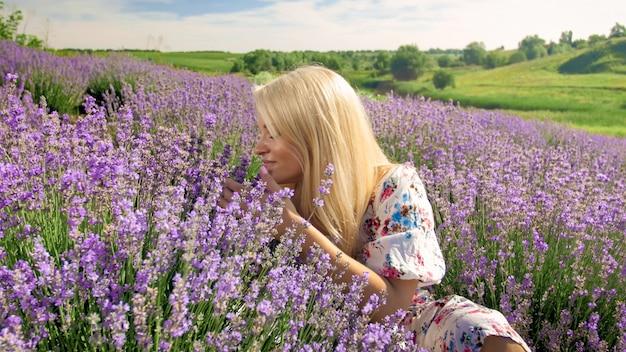 Retrato de mujer joven sonriente que huele flores en campo de lavanda en la provenza.