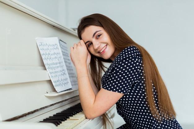Retrato de una mujer joven sonriente que se inclina en el piano que mira a la cámara
