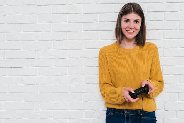 Retrato de una mujer joven sonriente que juega al videojuego con la palanca de mando que se opone a la pared de ladrillo blanca