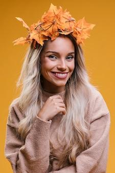 Retrato de la mujer joven sonriente que lleva la tiara de las hojas de arce contra la pared amarilla