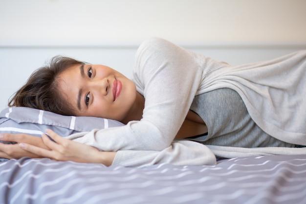 Retrato de la mujer joven sonriente que miente en cama