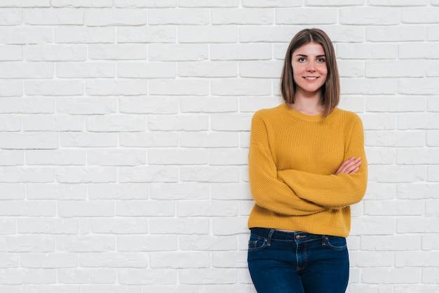 Retrato de una mujer joven sonriente que se opone a la pared blanca que mira la cámara