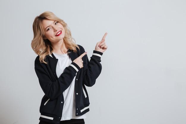 Retrato de una mujer joven sonriente que señala el dedo lejos
