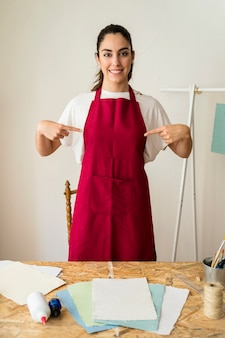 Retrato de una mujer joven sonriente que señala los dedos en su delantal rojo