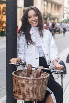 Retrato de una mujer joven sonriente que se sienta en la bicicleta en la calle