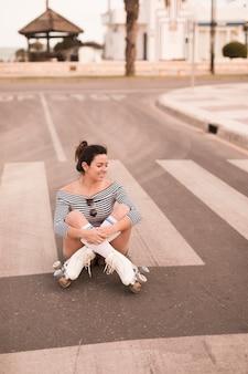 Retrato de una mujer joven sonriente que se sienta en el camino con sus piernas cruzadas que miran lejos