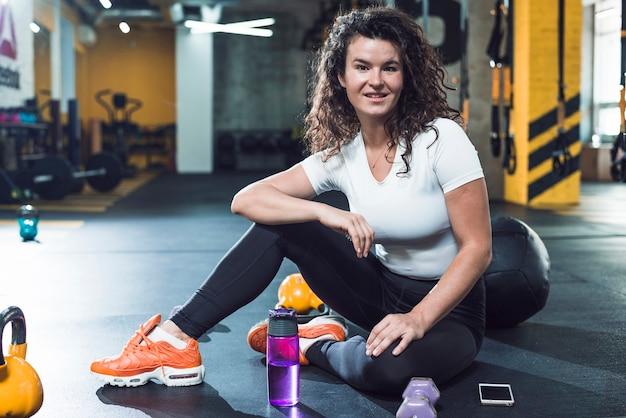 Retrato de una mujer joven sonriente que se sienta en piso en gimnasio