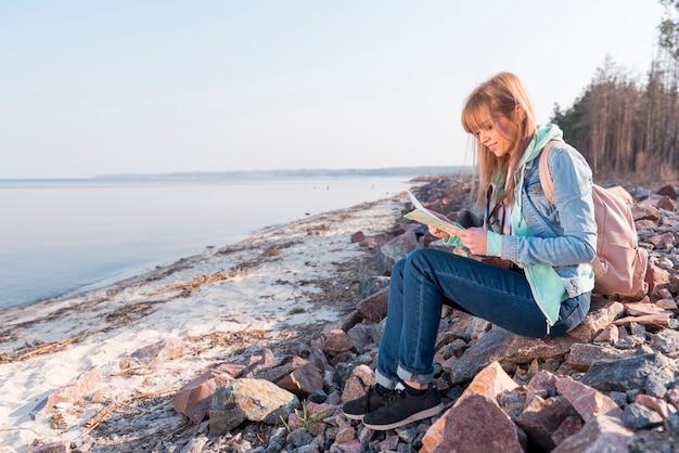 Retrato de una mujer joven sonriente que se sienta en la playa que mira el mapa