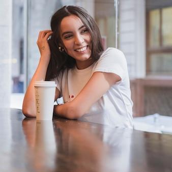 Retrato de una mujer joven sonriente que se sienta en la tabla con la taza de café para llevar en la tabla de madera