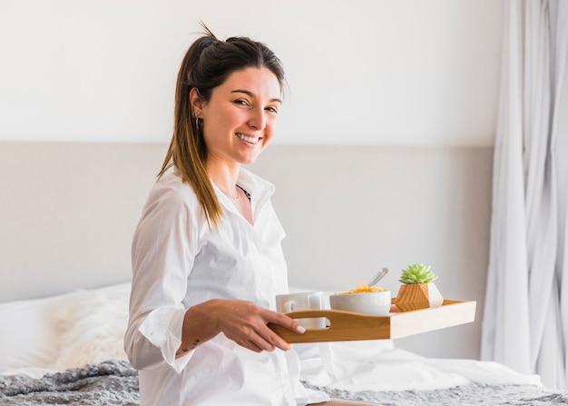 Retrato de una mujer joven sonriente que sostiene la bandeja del desayuno