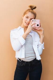 Retrato de una mujer joven sonriente que sostiene la cámara instantánea rosada contra el contexto beige