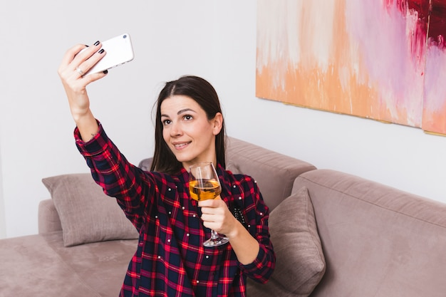 Retrato de una mujer joven sonriente que sostiene la copa que toma el selfie en el teléfono móvil en casa