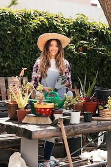 Retrato de una mujer joven sonriente que sostiene los guantes que cultivan un huerto que se colocan detrás de las plantas en la tabla