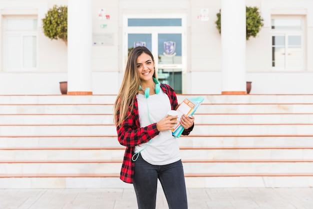 Retrato de una mujer joven sonriente que sostiene los libros en la mano que se opone al edificio de la universidad