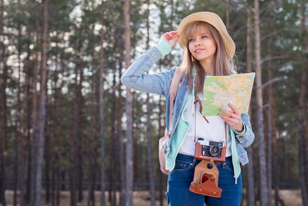 Retrato de una mujer joven sonriente que sostiene el mapa en la mano