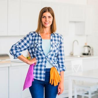 Retrato de la mujer joven sonriente que sostiene la servilleta rosada con los guantes de las naranjas que cuelgan sobre los vaqueros