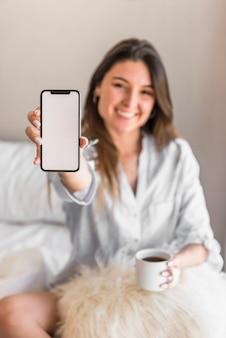Retrato de una mujer joven sonriente que sostiene la taza de café que muestra la pantalla del teléfono inteligente