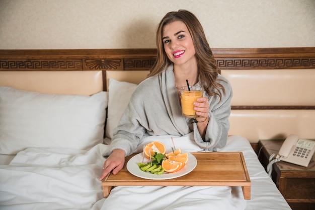 Retrato de una mujer joven sonriente que tiene fruta sana y un zumo de naranja en cama