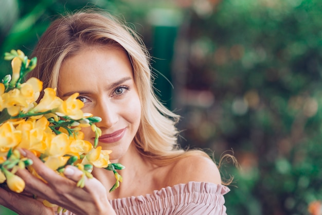 Retrato de una mujer joven sonriente que toca las flores amarillas de fresia con cuidado