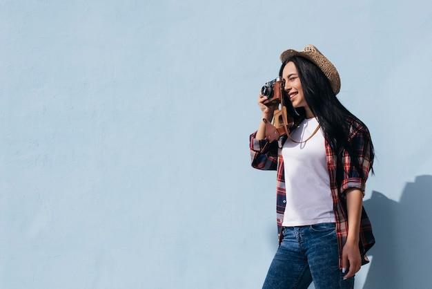 Retrato de una mujer joven sonriente que toma una foto con la cámara de pie cerca de la pared azul