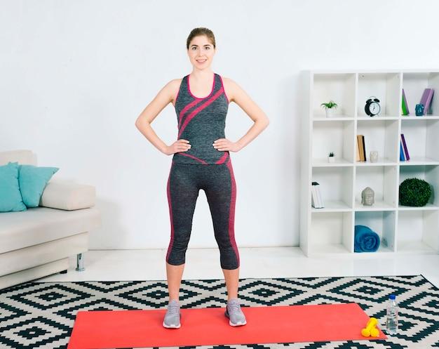 Retrato de la mujer joven sonriente en la ropa de deportes que se coloca en la estera del ejercicio