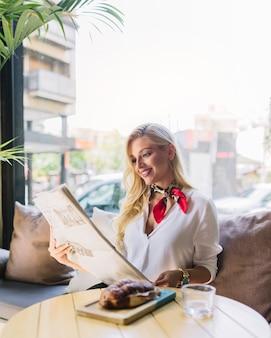Retrato de una mujer joven sonriente sentada en el café leyendo el periódico