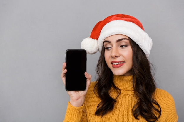 Retrato de una mujer joven sonriente con sombrero rojo de santa claus que se encuentran aisladas sobre fondo gris, mostrando teléfono móvil con pantalla en blanco