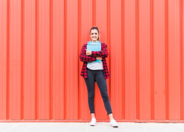 Retrato de una mujer joven sonriente sosteniendo libros en la mano de pie contra una pared naranja