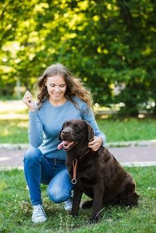 Retrato de una mujer joven sonriente y su perro en el jardín