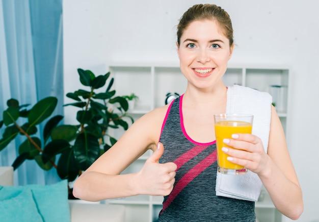 Retrato de una mujer joven sonriente con la toalla blanca sobre su hombro que sostiene el jugo de cristal que muestra el pulgar encima de la muestra