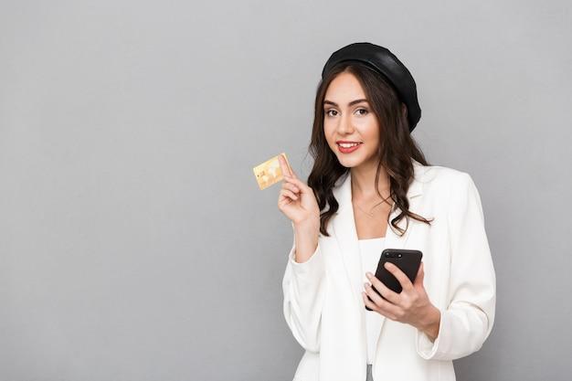 Retrato de una mujer joven sonriente vestida con chaqueta sobre fondo gris, sosteniendo el teléfono móvil, mostrando la tarjeta de crédito