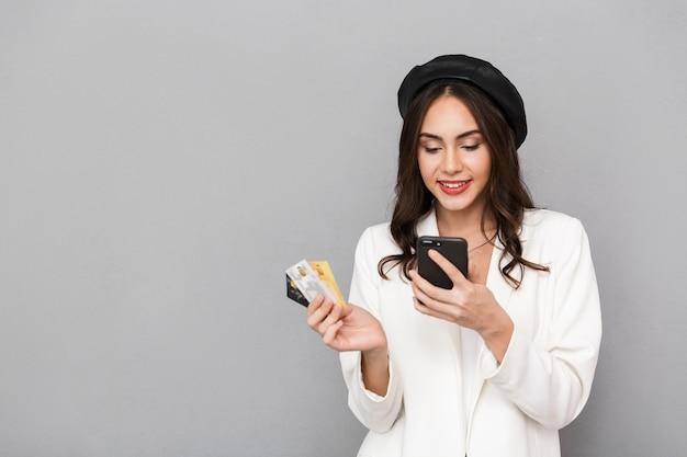 Retrato de una mujer joven sonriente vestida con chaqueta sobre fondo gris, mediante teléfono móvil, mostrando tarjetas de crédito