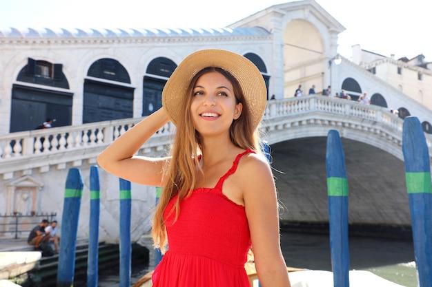 Retrato de mujer joven sonriente con un vestido rojo está de pie frente al famoso puente de rialto en venecia, italia