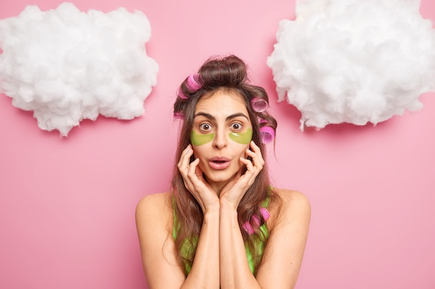 El retrato de una mujer joven sorprendida mira fijamente maravillado a la cámara aplica rizadores de pelo y parches de belleza debajo de los ojos mantiene las manos en la cara se prepara para la fiesta quiere lucir hermosa aislada sobre una pared rosa