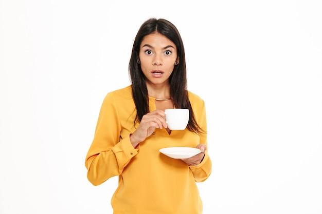 Retrato de una mujer joven sorprendida que sostiene la taza de té