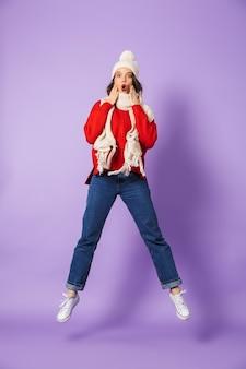 Retrato de una mujer joven sorprendida con sombrero de invierno aislado sobre pared púrpura saltando.
