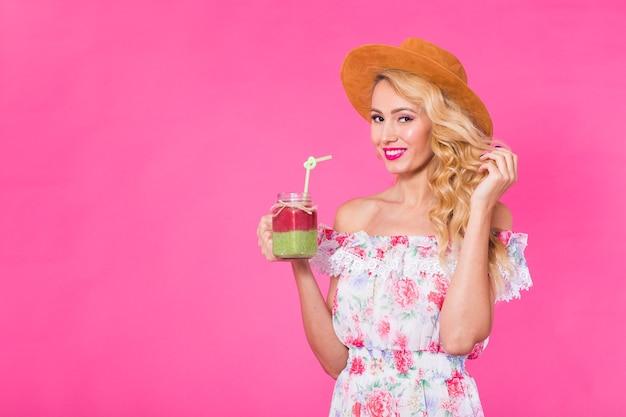 Retrato de mujer joven sosteniendo y bebiendo sabroso batido verde