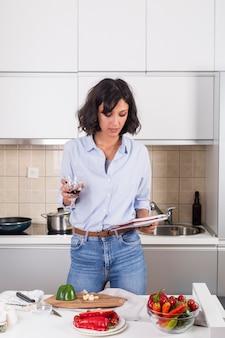 Retrato de una mujer joven sosteniendo una copa de vino en la mano leyendo la receta después de preparar la comida