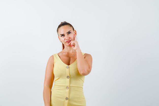 Retrato de mujer joven sosteniendo la mano en la barbilla, mirando hacia arriba con vestido amarillo y mirando pensativo vista frontal