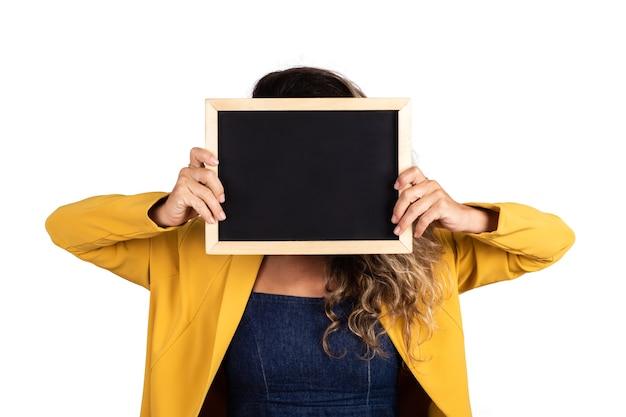 Retrato de mujer joven sosteniendo una pizarra vacía en estudio. fondo blanco aislado