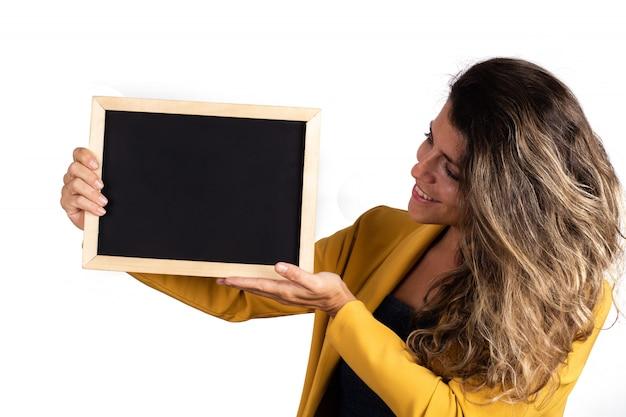 Retrato de mujer joven sosteniendo una pizarra vacía