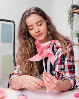 Retrato de una mujer joven sosteniendo polka origami rosa salpicado pinwheel