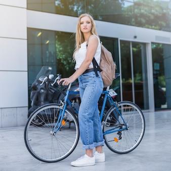 Retrato de mujer joven con su mochila de pie con bicicleta