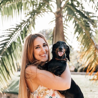 Retrato de una mujer joven con su perro mirando a la cámara
