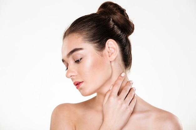 Retrato de mujer joven suave con cuerpo sano tocando su cuello posando con la cara hacia abajo